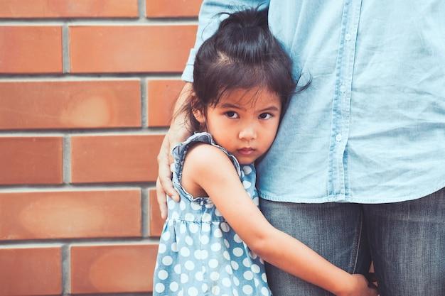 Trauriges asiatisches kindermädchen, das ihr mutterbein umarmt