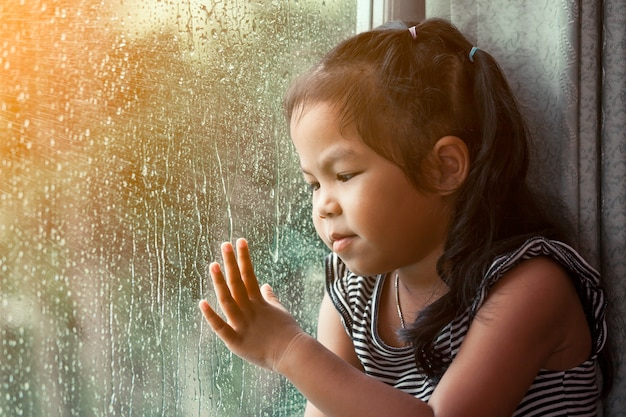 Trauriges asiatisches kleines mädchen, das draußen durch das fenster am regnerischen tag schaut