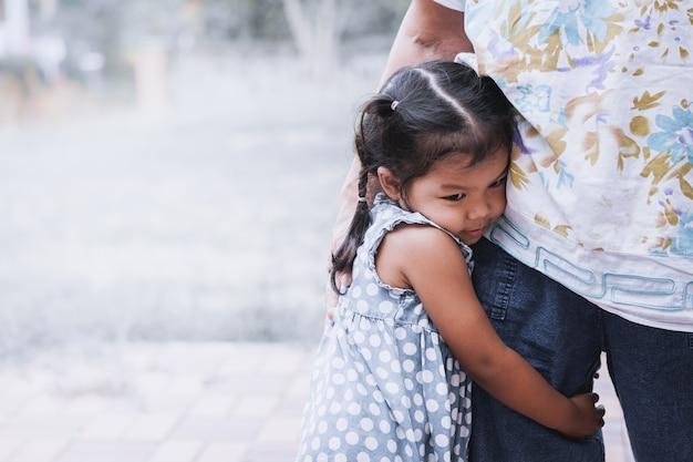 Trauriges asiatisches kleines mädchen, das ihr mutterbein im weinlesefarbton umarmt