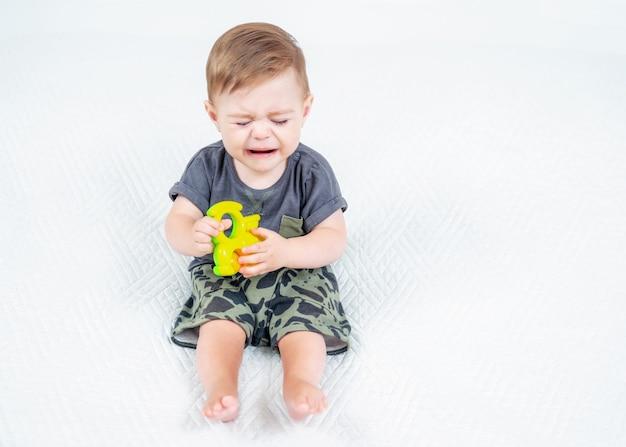 Trauriges baby in einem khaki-anzug mit buntem rasselspielzeug, das auf dem bett sitzt und weint
