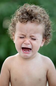 Trauriges baby mit dem weinen des gelockten haares