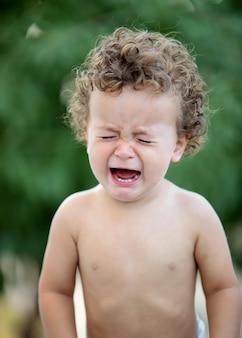 Trauriges baby mit dem weinen des lockigen haares
