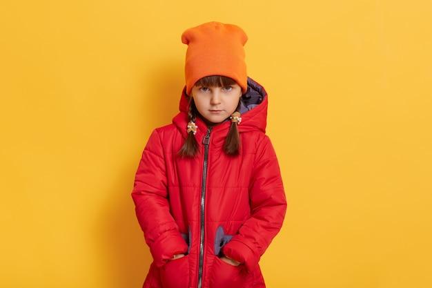 Trauriges beleidigtes kleines mädchen, das orange orange und rote jacke trägt, die gegen gelbe wand stehen und vorne mit verärgertem gesichtsausdruck schaut