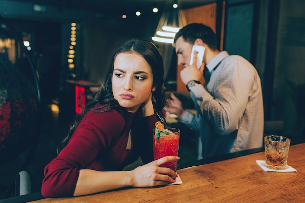Trauriges bild des mädchens, das nach rechts schaut. sie ist traurig, weil der mann auf den anruf antwortet und keine zeit mit ihr verbringt. sie hat keine gute laune.