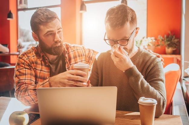 Trauriges bild von den kerlen, die auf dem tisch im café sitzen. einer von ihnen wurde krank und nieste mit einer serviette, während ein anderer seinen freund auffordert, kaffee zu trinken. nahansicht