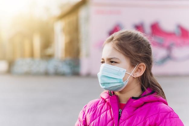 Trauriges, depressives kleines mädchen im sterilen medizinischen schutz vor virusmaske im freien. gesundheitswesen, epidemie, pandemie, krankheitskonzept