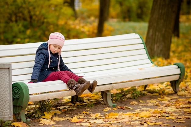 Trauriges einsames kindermädchen, das auf bank im park sitzt