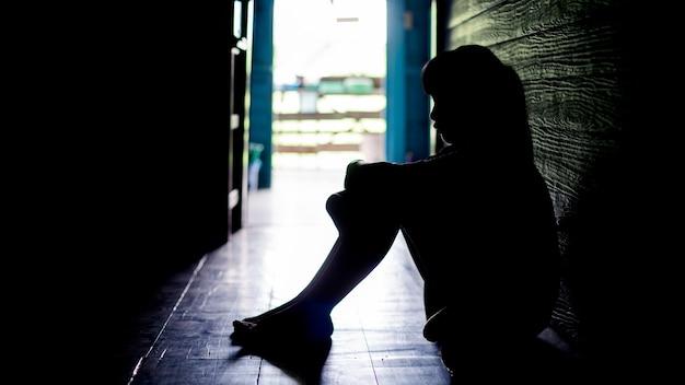 Trauriges einsames kleines mädchen, das weint, während es in einem dunklen raum mit einer haltung der traurigkeit auf dem boden sitzt. konzept von depression oder häuslicher gewalt kind