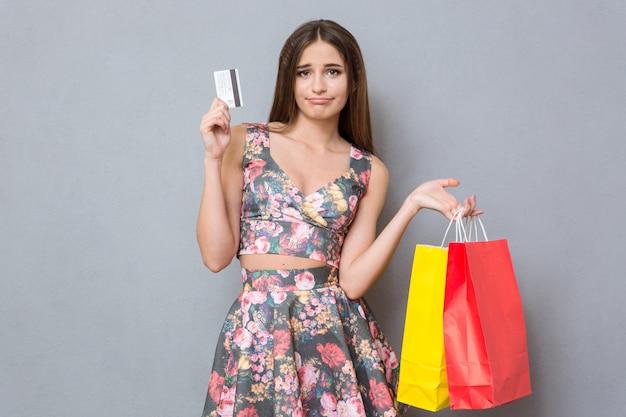 Trauriges enttäuschtes hübsches mädchen mit kreditkarte und bunten taschen