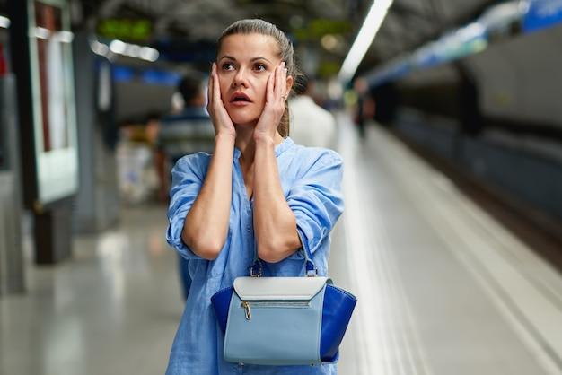 Trauriges frauenporträt innerhalb der u-bahn, die auf dem bahnsteig eines bahnhofs wartet, damit zug ankommt.