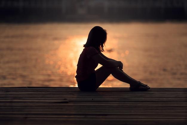 Trauriges frauenschattenbild gesorgt bei sonnenuntergang