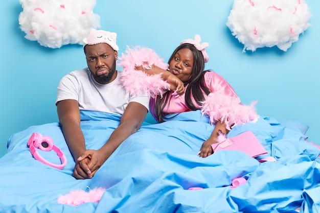 Trauriges, gelangweiltes, unglückliches afroamerikanisches paar bleibt in einem bequemen bett und verbringt das wochenende zu hause, lässig gekleidet isoliert auf blau