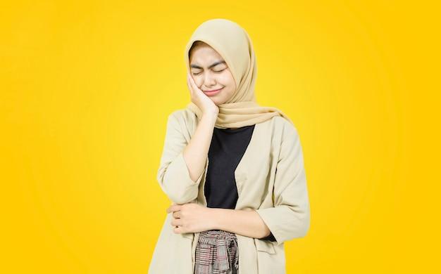 Trauriges gesicht der asiatischen jungen frau auf gelber wand