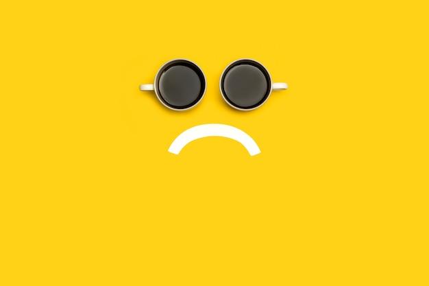 Trauriges gesicht mit zwei tassen kaffee auf gelbem hintergrund