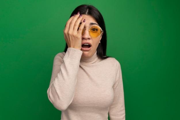 Trauriges hübsches brünettes kaukasisches mädchen in der sonnenbrille hält hand vor auge, das kamera auf grün betrachtet