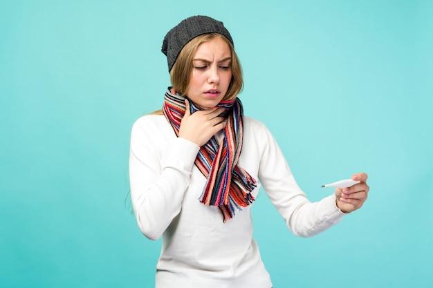 Trauriges jugendlich mädchen, das rauchgas nimmt thermometer gegen blauen raum. schöne dame ist krank mit einer hohen temperatur, isolierte nahaufnahme.
