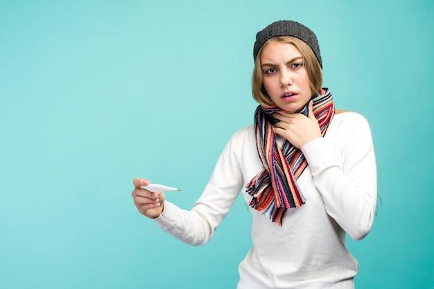 Trauriges jugendlich mädchen, das rauchthermometer gegen blauen hintergrund nimmt. schöne dame ist krank mit einer hohen temperatur, isolierte nahaufnahme. - bild