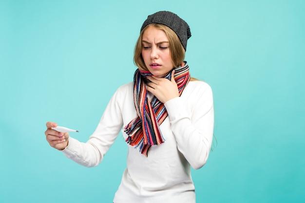 Trauriges jugendlich mädchen, das rauchthermometer gegen blauen hintergrund nimmt