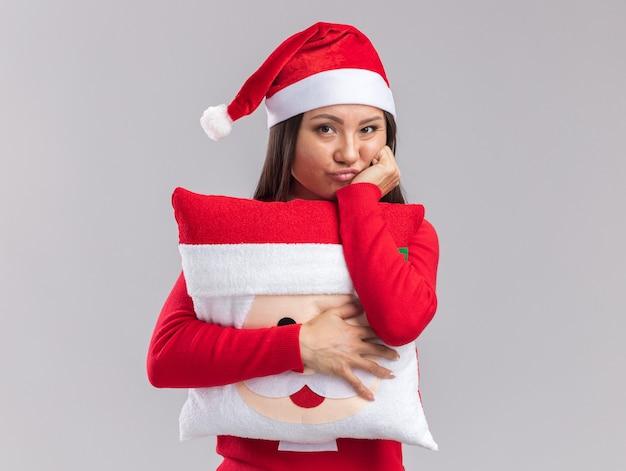 Trauriges junges asiatisches mädchen mit weihnachtsmütze mit pullover mit weihnachtskissen, das hand auf die wange legt, isoliert auf weißem hintergrund