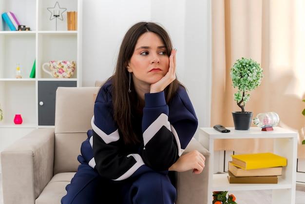Trauriges junges hübsches kaukasisches mädchen, das auf sessel in entworfenem wohnzimmer sitzt, das seite betrachtet und hand unter kinn legt