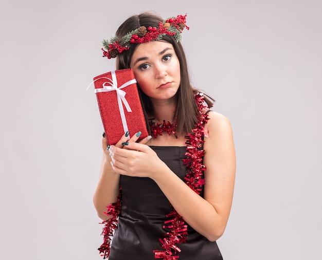 Trauriges junges hübsches kaukasisches mädchen, das weihnachtskopfkranz und lametta-girlande um den hals trägt, das geschenkpaket hält, das das gesicht berührt und dabei die kamera einzeln auf weißem hintergrund mit kopienraum betrachtet
