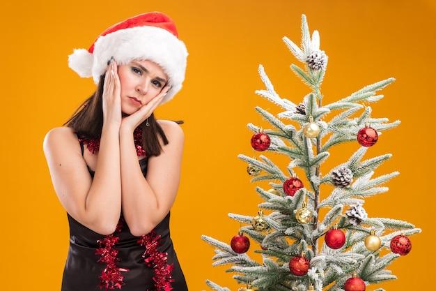 Trauriges junges hübsches kaukasisches mädchen mit weihnachtsmütze und lametta-girlande um den hals, das in der nähe des geschmückten weihnachtsbaums steht und die hände auf dem gesicht hält und die kamera einzeln auf orangefarbenem hintergrund betrachtet