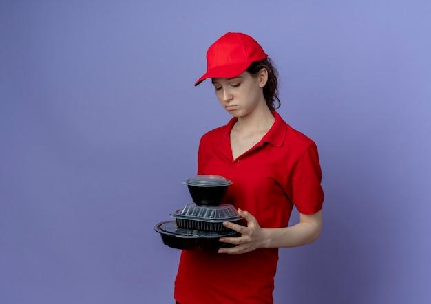 Trauriges junges hübsches liefermädchen, das rote uniform und kappe hält und lebensmittelbehälter lokalisiert auf lila hintergrund mit kopienraum hält