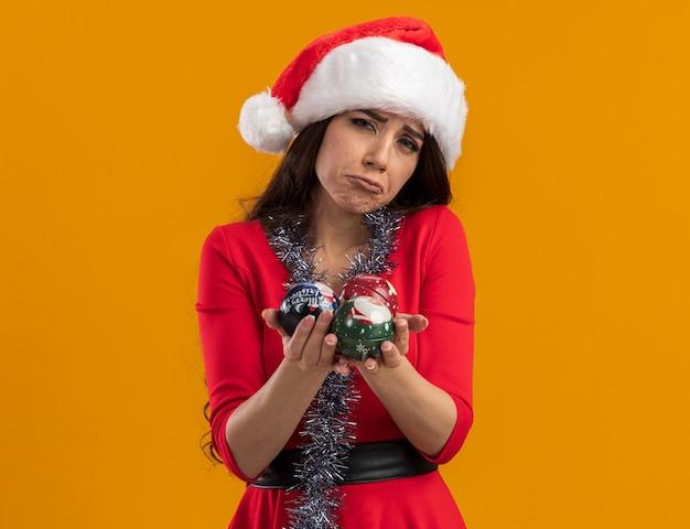 Trauriges junges hübsches mädchen mit weihnachtsmütze und lametta-girlande um den hals, das weihnachtskugeln isoliert auf oranger wand mit kopierraum hält