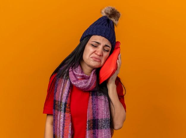 Trauriges junges kaukasisches krankes mädchen, das wintermütze und schal berührendes gesicht mit heißem wassersack mit geschlossenen augen trägt, lokalisiert auf orange wand mit kopienraum
