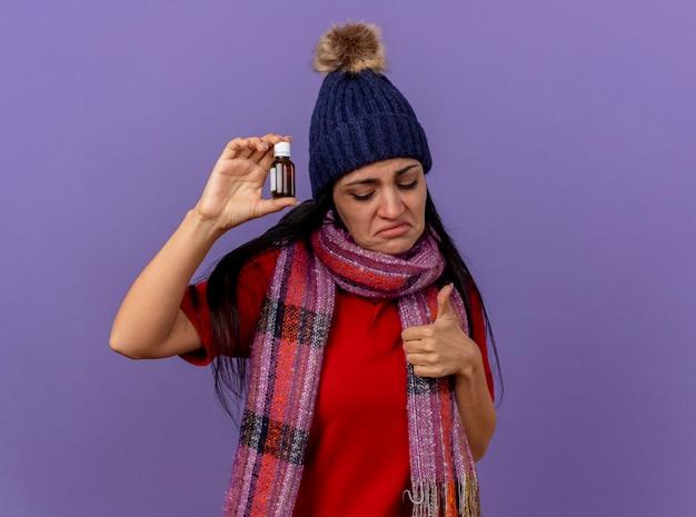 Trauriges junges kaukasisches krankes mädchen, das wintermütze und schal hält, das medikament im glas hält, das unten zeigt daumen oben auf lila wand mit kopienraum zeigt