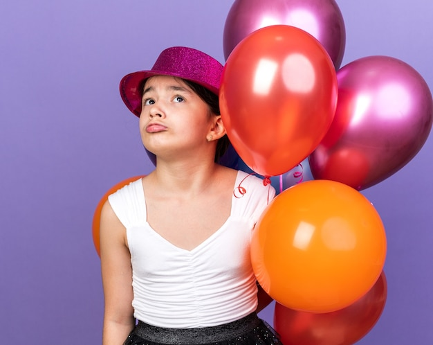 Trauriges junges kaukasisches mädchen mit violettem partyhut, der heliumballons hält und lokalisiert auf lila wand mit kopienraum sucht