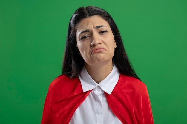 Trauriges junges kaukasisches superheldenmädchen, das rechts ohne handzeichen lokalisiert auf grüner wand steht
