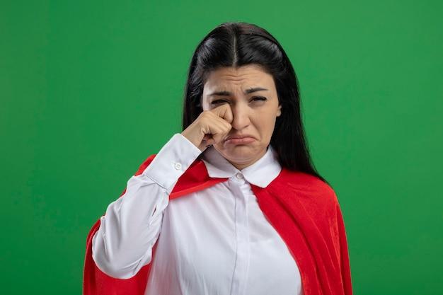 Trauriges junges kaukasisches superheldenmädchen, das weint und ihre tränen abwischt, die auf grüner wand mit kopienraum isoliert werden