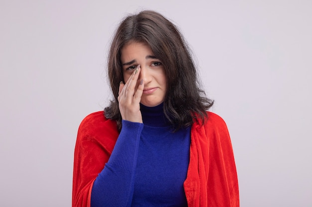 Trauriges junges kaukasisches superheldenmädchen im roten umhang, das hand auf die nase legt, die auf weißer wand lokalisiert wird