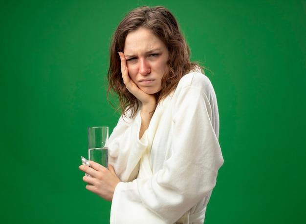 Trauriges junges krankes mädchen, das geradeaus schaut und weißes gewand trägt, das glas wasser hält, das hand auf wange lokalisiert auf grün hält