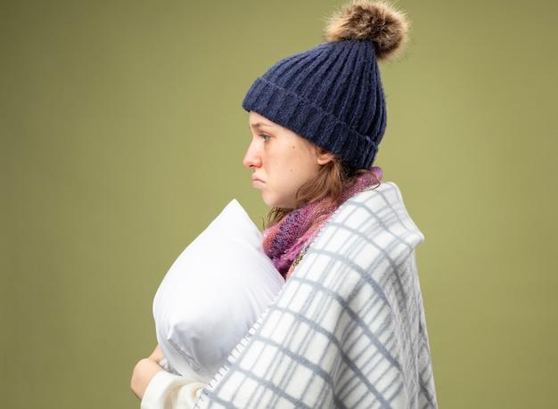 Trauriges junges krankes mädchen, das in der profilansicht steht und weißes gewand und wintermütze mit schal trägt, der im karierten umarmten kissen eingewickelt wird
