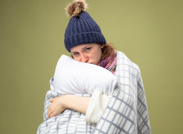 Trauriges junges krankes mädchen, das weiße robe und wintermütze mit schal wickelt, der im karierten umarmten kissen eingewickelt wird