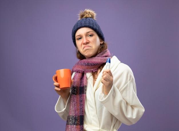 Trauriges junges krankes mädchen, das weißes gewand und wintermütze mit schal hält tasse des tees mit thermometer lokalisiert auf lila trägt