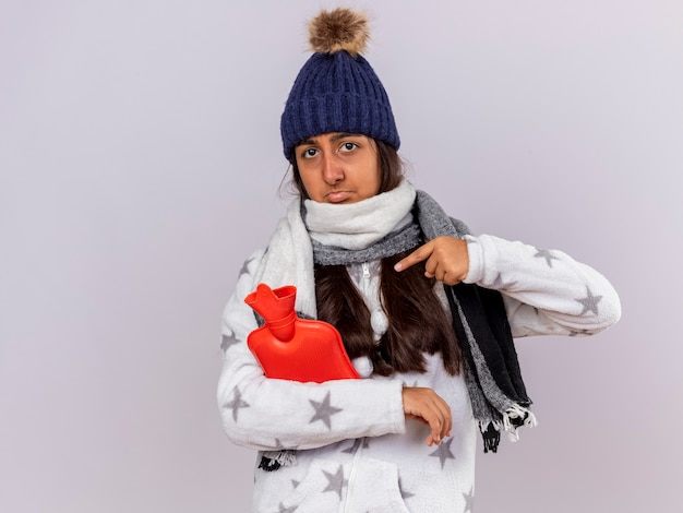Trauriges junges krankes mädchen, das wintermütze mit schal hält und punkte auf heißwassersack lokalisiert auf weißem hintergrund mit kopienraum trägt Kostenlose Fotos