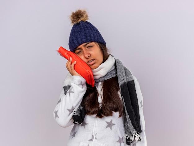 Trauriges junges krankes mädchen, das wintermütze mit schal trägt, der heißen wasserbeutel auf wange lokalisiert auf weißem hintergrund setzt Kostenlose Fotos