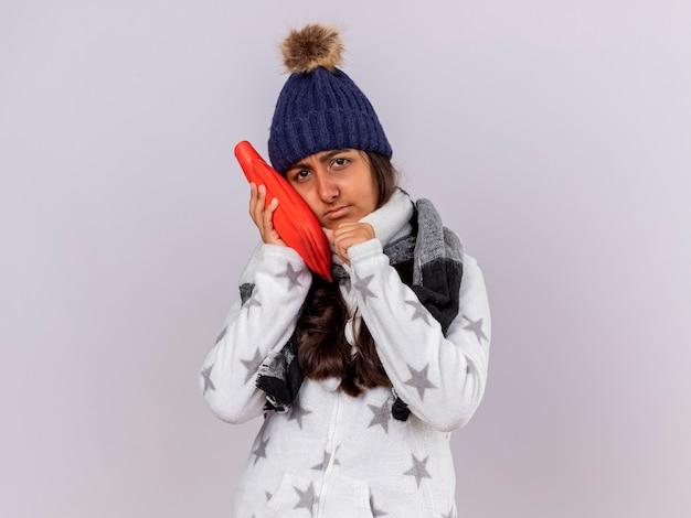 Trauriges junges krankes mädchen, das wintermütze mit schal trägt, der heißen wassersack auf wange lokalisiert auf weiß setzt