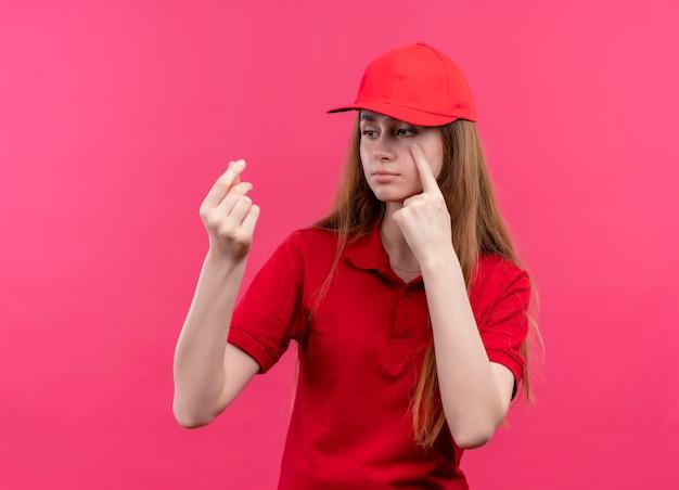 Trauriges junges liefermädchen in der roten uniform, die geld tut und geste auf isoliertem rosa raum weint