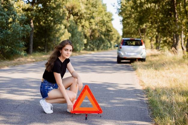 Trauriges junges mädchen, das rotes notauszeichen nahe defektem silbernem auto auf die straße setzt