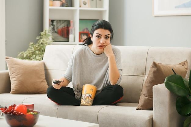 Trauriges, junges mädchen mit popcorn-eimer, das die hand auf die wange legt, die tv-fernbedienung hält, die auf dem sofa hinter dem couchtisch im wohnzimmer sitzt?