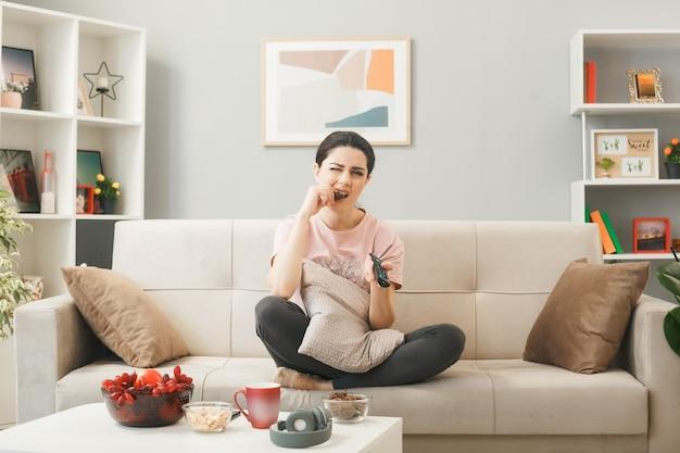 Trauriges junges mädchen mit tv-fernbedienung beißt keks ab, das auf dem sofa hinter dem couchtisch im wohnzimmer sitzt