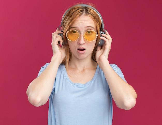 Trauriges junges rothaariges ingwermädchen mit sommersprossen in sonnenbrillen und auf kopfhörern isoliert auf rosa wand mit kopierraum