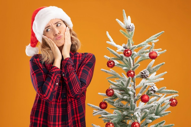 Trauriges junges schönes mädchen, das in der nähe des weihnachtsbaums mit weihnachtsmütze steht und die hände auf die wangen legt, isoliert auf orangefarbenem hintergrund