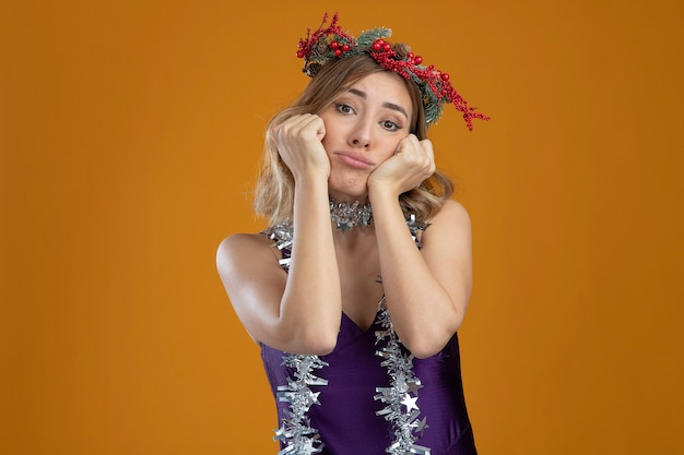 Trauriges junges, schönes mädchen, das lila kleid mit kranz trägt, das die hände auf die wangen legt, isoliert auf braunem hintergrund