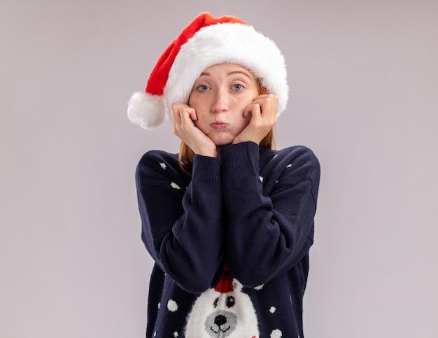 Trauriges junges schönes mädchen, das weihnachtsmütze und brille trägt, die hände auf wangen lokalisiert auf weißem hintergrund setzen