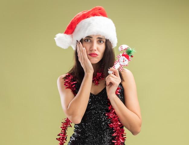 Trauriges junges schönes mädchen mit weihnachtsmütze mit girlande am hals, das weihnachtsspielzeug hält, das hand auf die wange legt, isoliert auf olivgrünem hintergrund